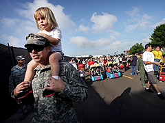 EDMUND D. FOUNTAIN—TAMPA BAY TIMES/AP Soldier Donnie Terrell, a member of the U.S. Army, carries his daughter Hailey during a parade at MacDill Air Force Base in Tampa, Florida.